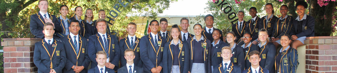 We are proud of our Prefects - here one past year's Student Leadership poses by the school entrance